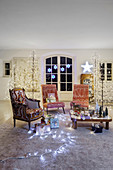 Living room festively decorated with fairy lights and stylised illuminated Christmas trees
