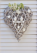 Welcome sign made of woven-vine heart with lilac flowers and metal heart