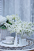White lilac bouquet on the patio table in the winter garden