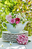 Early summer bouquet with peonies, carnations and whistle bush in teapot