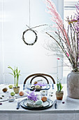 Easter table set with natural materials: eggs, grasses and twigs