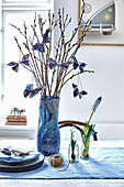 Blue vase of willow branches decorated with folded paper butterflies