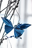 Blue folded paper butterfly hung from willow branch