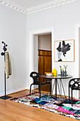 Runder, schwarzer Tisch mit Designerstühlen auf buntem Teppich