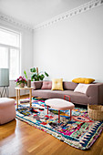 Scatter cushions on sofa, houseplants and side tables on multicoloured rug