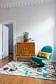 Sideboard and turquoise designer chair on Berber rug