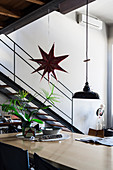 Pendant lamp and star decoration above pale dining table