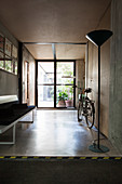 Standard lamp, bicycle and bench in foyer with concrete floor