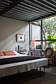 Double bed, bedroom bench and bookshelves below window in bedroom