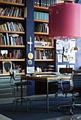 Schreibtisch mit Stühlen in Bibliothek mit dunelblauer Wand