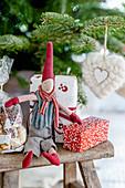 Wchtel und verpackte Geschenke auf dem Hocker vorm Weihnachtsbaum