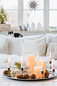 Arrangement of candles on tray and Christmas decorations in living room