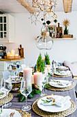Weihnachtlich gedeckter Tisch mit Koniferen und Blockkerzen
