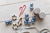 Candy canes, blue baubles, candles and pastry cutters