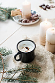 Hot drink in enamel mug anc candles on hessian fabric