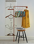 Arrangement of coat hangers bent into various shapes decorating wall and used as magazine holders