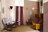 Ochre-yellow wing-back chair and rocking chair in interior decorated in shades of pink
