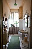 Schmales Bad in Altbauwohnung mit Stauraum hinter Vorhang unterm Fenster