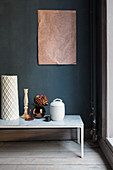 Ornaments on bench with marble top against dark blue wall