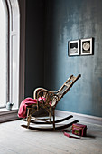 Rocking chair against dark blue wall and next to large arched window