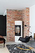 Cylindrical wood-burning stove against brick wall in living room