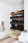 Shoes and boots on shoe rack fitted in niche