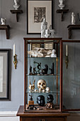 Collection of curiosities in display case and sculptures on bracket shelves