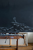 Dark painting on easel in artist's studio