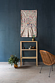 Painted wall hanging above shelves on dark blue wall