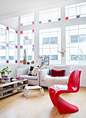 Red designer chair in living room with stained-glass window elements