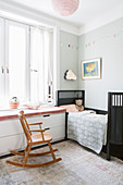 Rocking chair next to window seat with chest of drawers below in child's bedroom