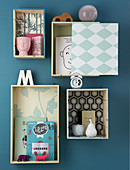 Shallow shelving modules covered in wallpaper with various patterns on wall