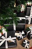 Christmas presents wrapped in black paper with white ribbons