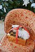 Wrapped presents decorated with ribbon, feathers and pine cones on easy chair