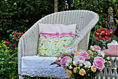 Cushion with hand-sewn cover on wicker armchair in summery garden