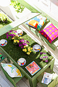 Flowers on table covered in artificial grass on terrace