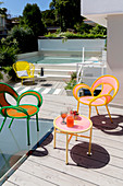 Colourful chairs and table on terrace with pool in background
