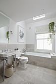Helles Badezimmer mit Vintage-Waschtisch, Toilette und eingebauter Badewanne unter Oberlicht