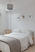 Simple double bed in bedroom with white walls