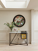 Round, abstract painting on wall above console table in interior with skylights