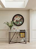 Abstraktes rundes Wandgemälde über Konsolentisch in Wohnraum mit Oberlichtfenstern