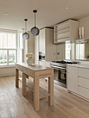 Simple, narrow kitchen island in pale wood in white, timeless kitchen