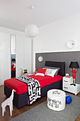 Box spring bed in black and red against grey checked wall in boy's bedroom