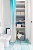 Storage shelves hidden behind curtain in bathroom