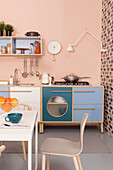 Kitchen counter with blue, white and turquoise cabinets against pastel-pink wall