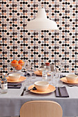 Set dining table in front of wall with grey, black and pink wallpaper with graphic pattern