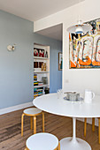 Abstract picture on wall above Tulip table and stacking stools in dining area