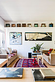 Linen sofas and kilim rug below pictures of whale and Mickey Mouse on wall