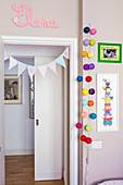 Dove-grey walls, bunting and colourful fairy lights decorating door of nursery