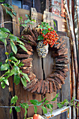 Wreath of tree bark decorated with rose hips and bird cake